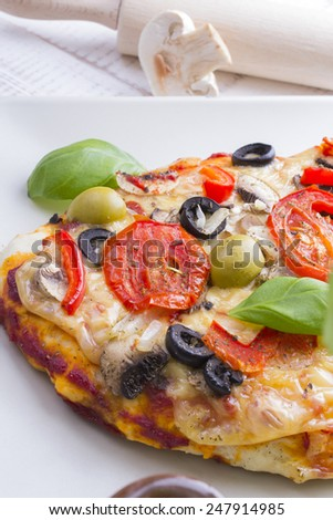 pizza with tomatoes, mushrooms, olives and peppers served on a plate on a wooden table