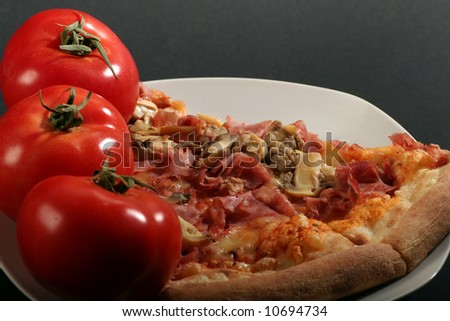Pizza with tomatoes on a black background.