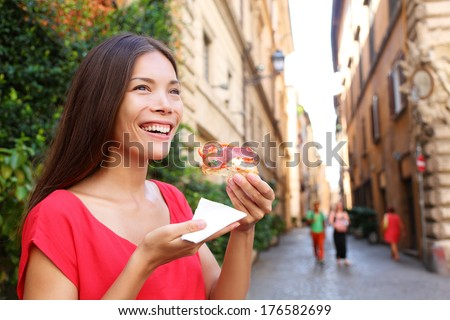 Pizza woman eating pizza slice in Rome, Italy smiling happy outdoors during travel vacation holiday. Beautiful mixed race Asian Caucasian woman enjoying Italian food. - stock photo