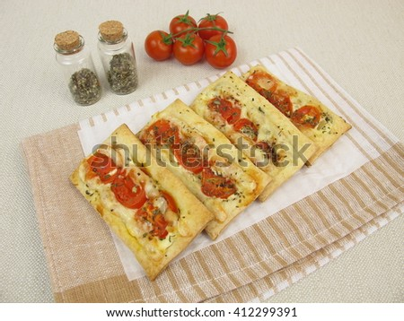 Pizzas from puff pastry with tomato and cheese