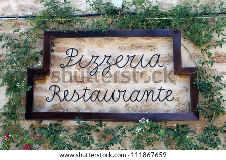 Pizzeria restuaurant sign on old wall surrounded by ivy, Italian or Spanish. - stock photo