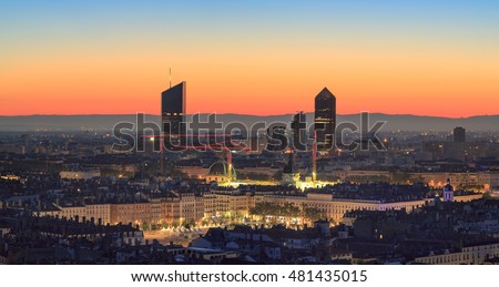 Place Bellecour and the towers of Part-Dieu in the city of Lyon, France, at dawn.