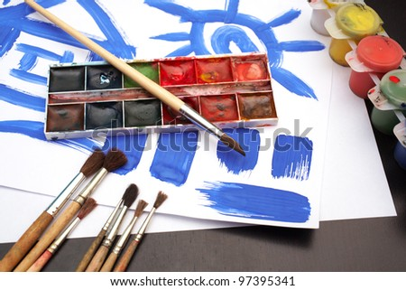 Place for a little painter: paint brushes, paints and picture on the table - stock photo