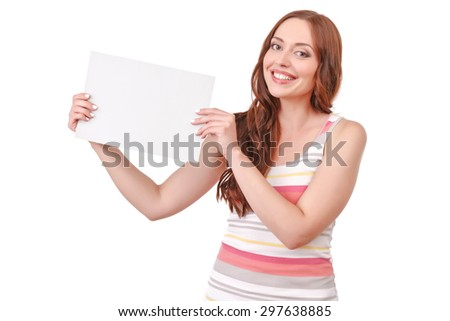 Place for advertisement. Happy smiling red-haired woman standing on white isolated background and holding paper board.