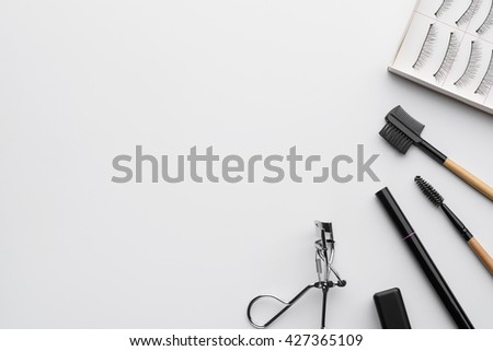 Place for lettering with brushes in the right corner of the shot. White background. False lashes, brushes, mascara and curler for application of make-up on eyes. - stock photo
