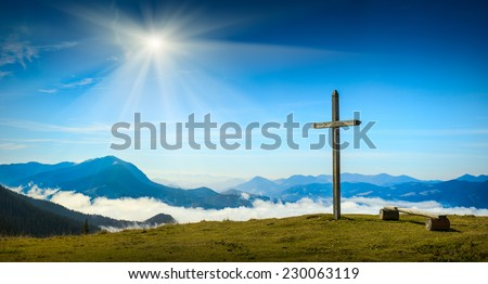 Place for rest with christian cross on a top of mountain above the sunny foggy valley. Carpathian mountains, Ukraine. - stock photo