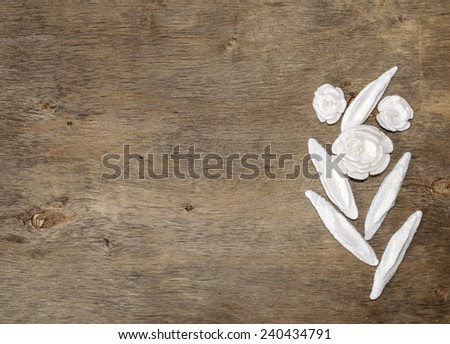 Place for text on wooden background and white floral pieces of white felt