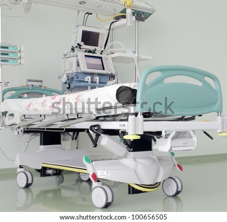 place in the intensive care unit, ready to receive patients. Medical multifunction bed, artificial respiration apparatus, monitor, panel of medical gases. - stock photo