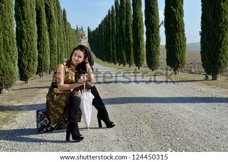 Place of destination. Stylish young woman sits on the suitcase on a rural road along cypress alley. Tuscan, Italy - stock photo