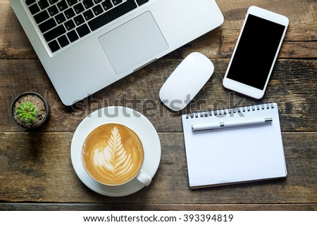 Place of work. Close-up top view of comfortable working place in office with wooden table and laptop coffee of cup smart phone notepad and mouse  laying on it - stock photo