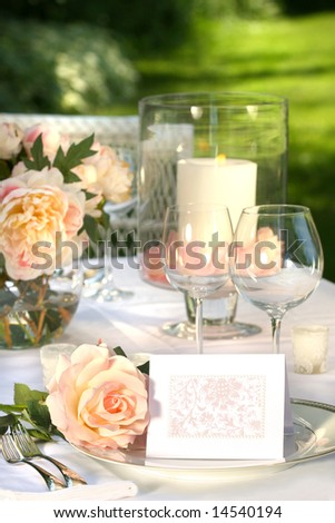 Place setting and card on a table at a wedding reception - stock photo