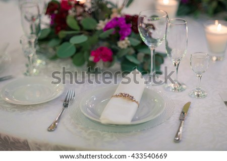 Place setting and wine on rustic wood table - stock photo