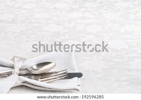 Place setting Closeup with fork, knife, spoon, white napkin in lower left on damask tablecloth background with room or space for copy, text.  Horizontal - stock photo