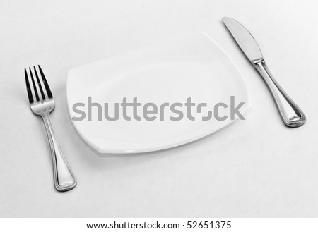 Place setting for one person. Knife, square white plate and fork. - stock photo
