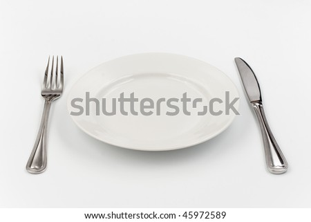 Place setting for one person. Knife, white plate and fork. - stock photo
