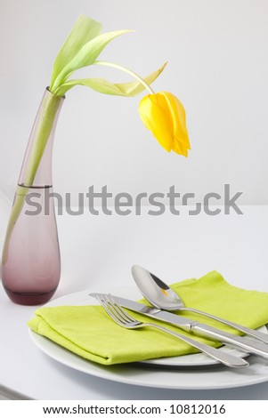 Place setting in green with yellow tulip - stock photo