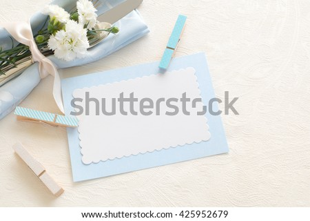 Place setting of Silverware, blue napkin, blank name card held by clothespins, carnations on side on white tablecloth with room or space for copy, text, your words. Horizontal top aerial view