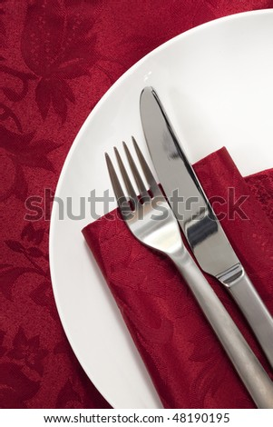 Place setting on red damask tablecloth.