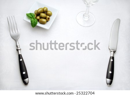 Place setting on white cloth with green olives with empty space for plate
