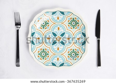 Place setting on white tablecloth - stock photo