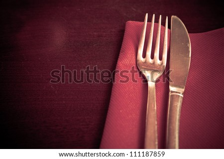 place setting - plate, knife and fork on table - stock photo