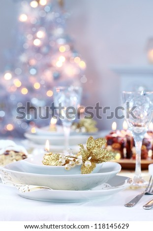 Place setting with Christmas tree in background - stock photo