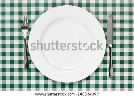 place setting with empty plate, knife and fork on green gingham background popular symbol for diners and cafes
