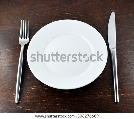 Place setting with fork and knife on rustic wooden table