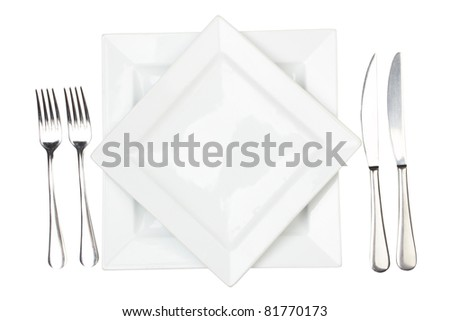 Place setting with high-gloss plate, knife & fork. Isolated on white. - stock photo