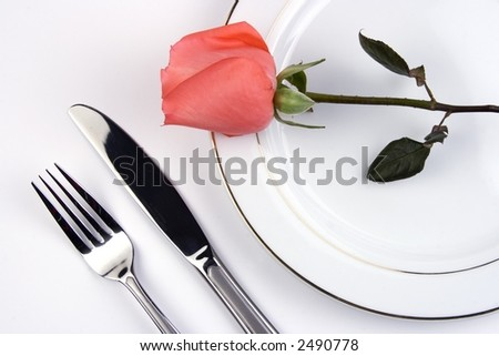 Place setting with pinky rose in white background. - stock photo