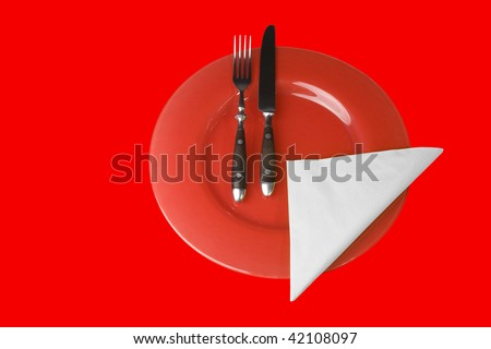 Place setting with plate, fork and knife red on red, with white napkin - stock photo
