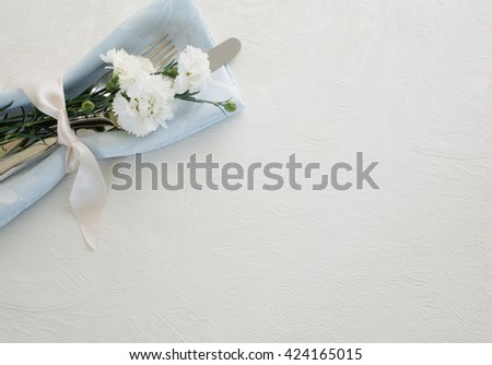 Place setting with Silverware, pastel blue napkin, and carnation flowers in top corner on textured white tablecloth background with room or space for copy, text, your words.  Horizontal aerial view