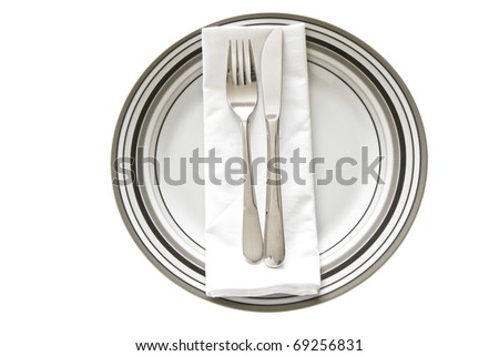 Place Setting with striped printed dinner plate, cutlery and serviette isolated on a white background - stock photo