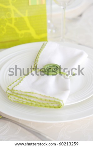Place setting with white napkin decorated with green button