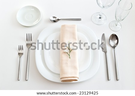 place setting with white plates forks glasses beige napkin and little flower - stock photo
