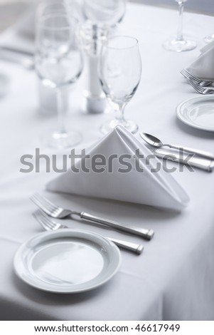 Place settings on an elegant, white dining table in a restaurant. Vertical shot. - stock photo