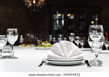 Place settings with two plates, three glasses, napkin, knife and fork - stock photo