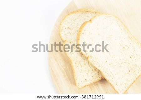 Place the bread on wood isolated white backdrop. - stock photo