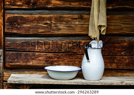 Place to wash up with white jug and bowl for water and a rugged cloth to dry with. Timber facade with copy space. - stock photo