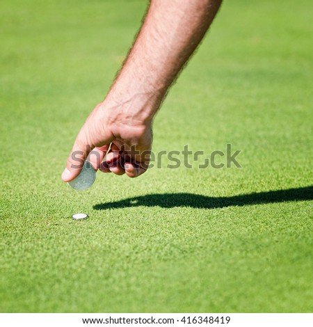 Placing golf ball on the green - stock photo