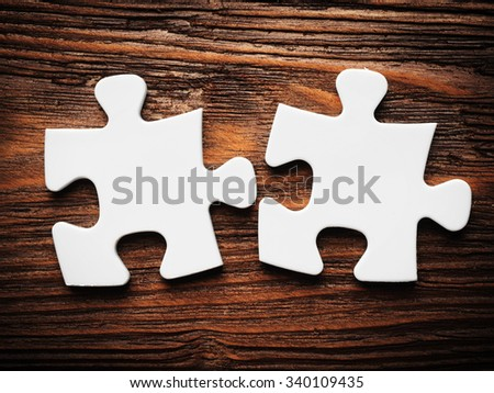 Placing missing a piece of puzzle. business concept. wooden background - stock photo
