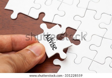 Placing missing a piece of puzzle with advise word - stock photo