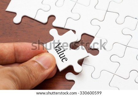 Placing missing a piece of puzzle with value word - stock photo
