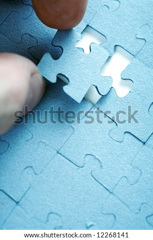 Placing puzzle piece into correct place - stock photo