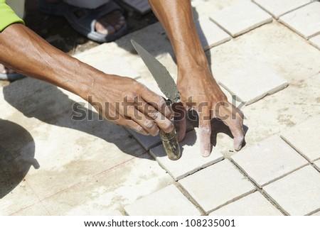 Placing the floor tiles - stock photo