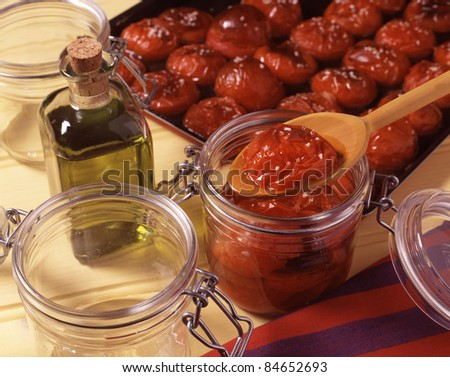 Placing the tomatoes in the jars and add the olive oil