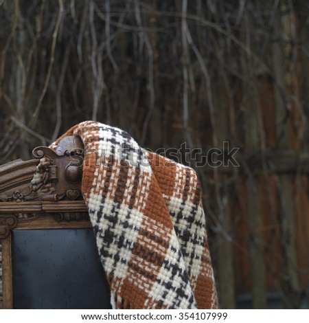 Plaid on antique chair, garden in the blurred background, concept of relaxation
