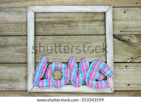Plaid pink and blue fabric word LOVE on wooden rustic frame background