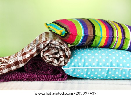 Plaids and color pillows on green background