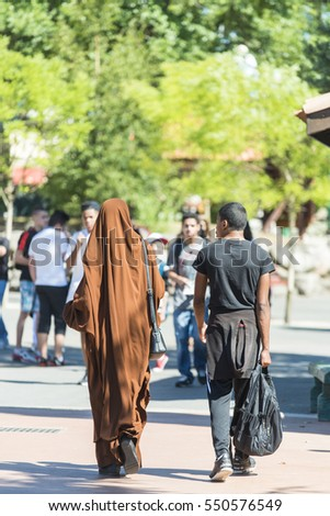 PLAILLY, FRANCE - JULY 10, 2015: A couple with Arab dress walk in a amusement park.